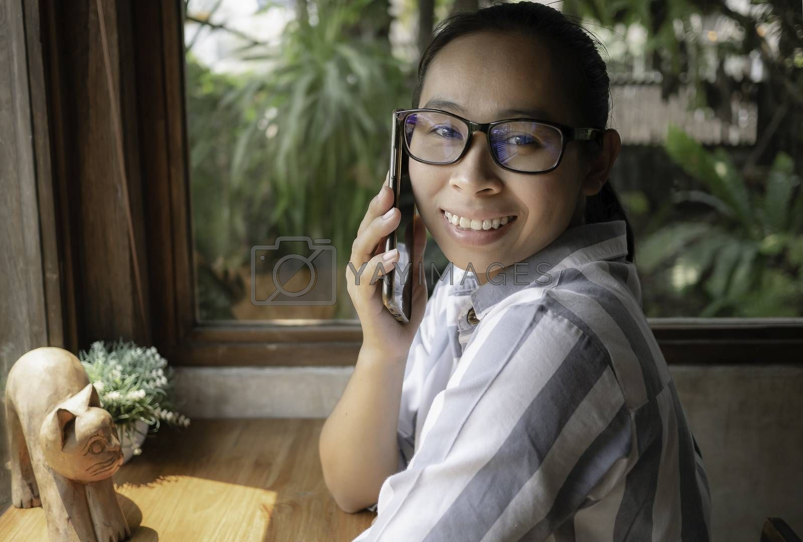 Cheerful Asian young woman talking on the phone at coffee cafe, smiling face.