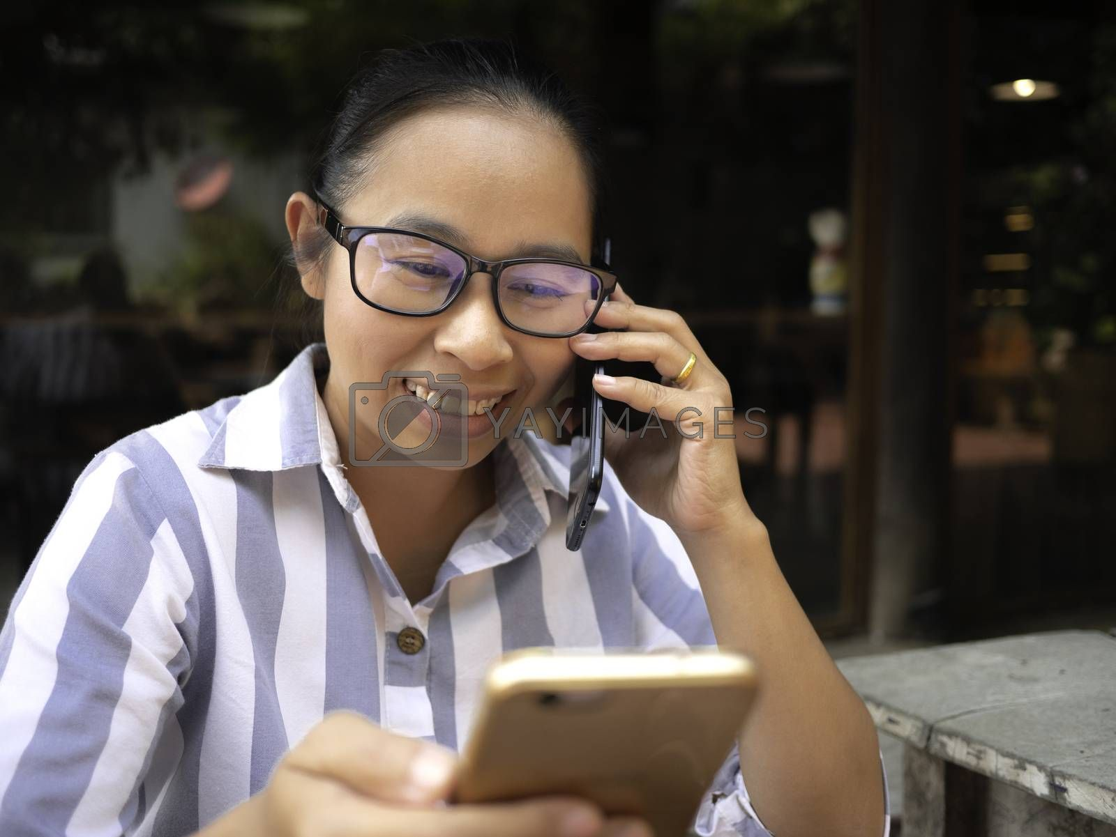 Cheerful business Asian young woman holding smartphone for work while talking on the phone at coffee cafe, Happy and smile face. by TEERASAK