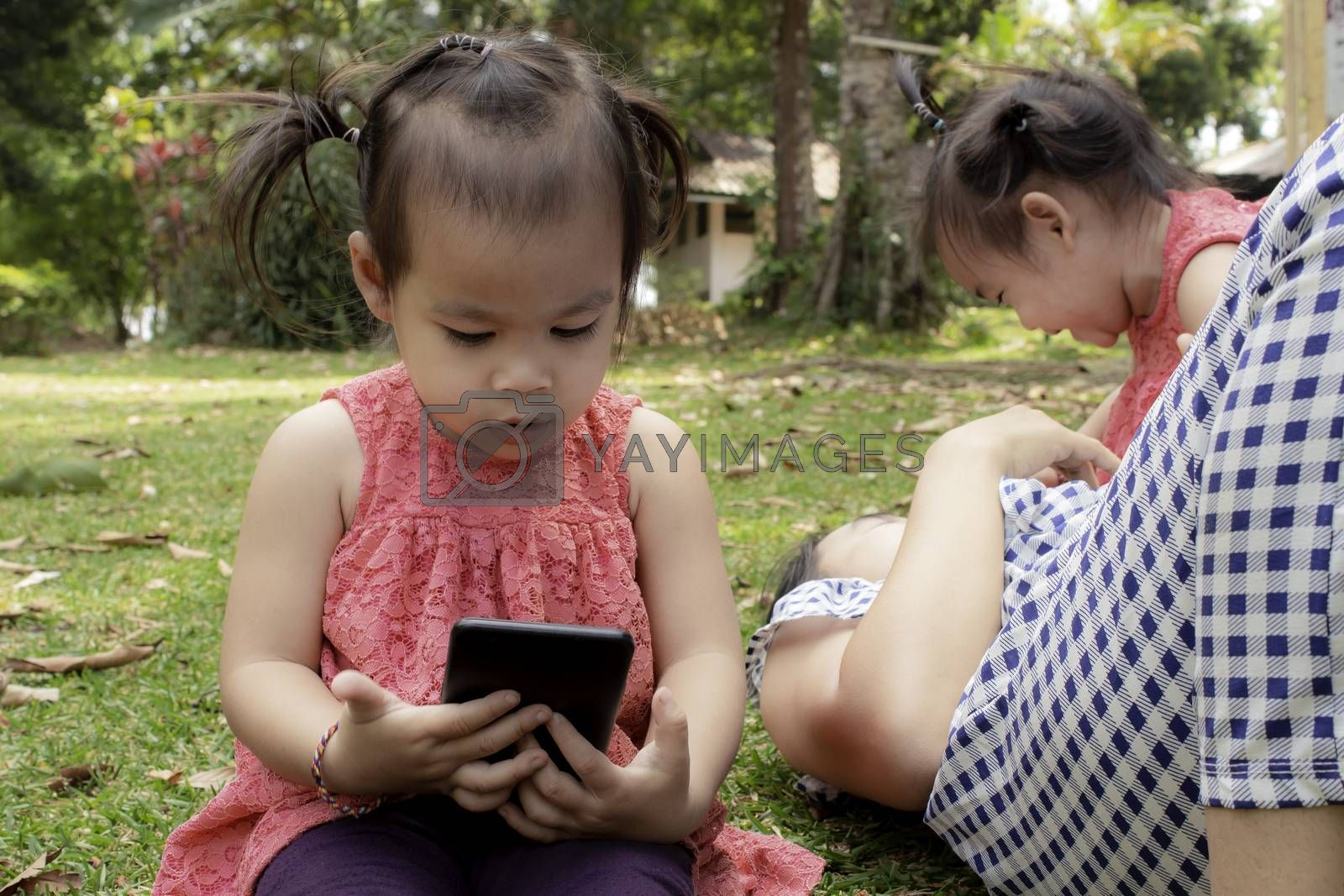 Asian little girl sitting on the grasses ground in the garden and looking at smartphone happily while mother and sister lying down to play  near. by TEERASAK