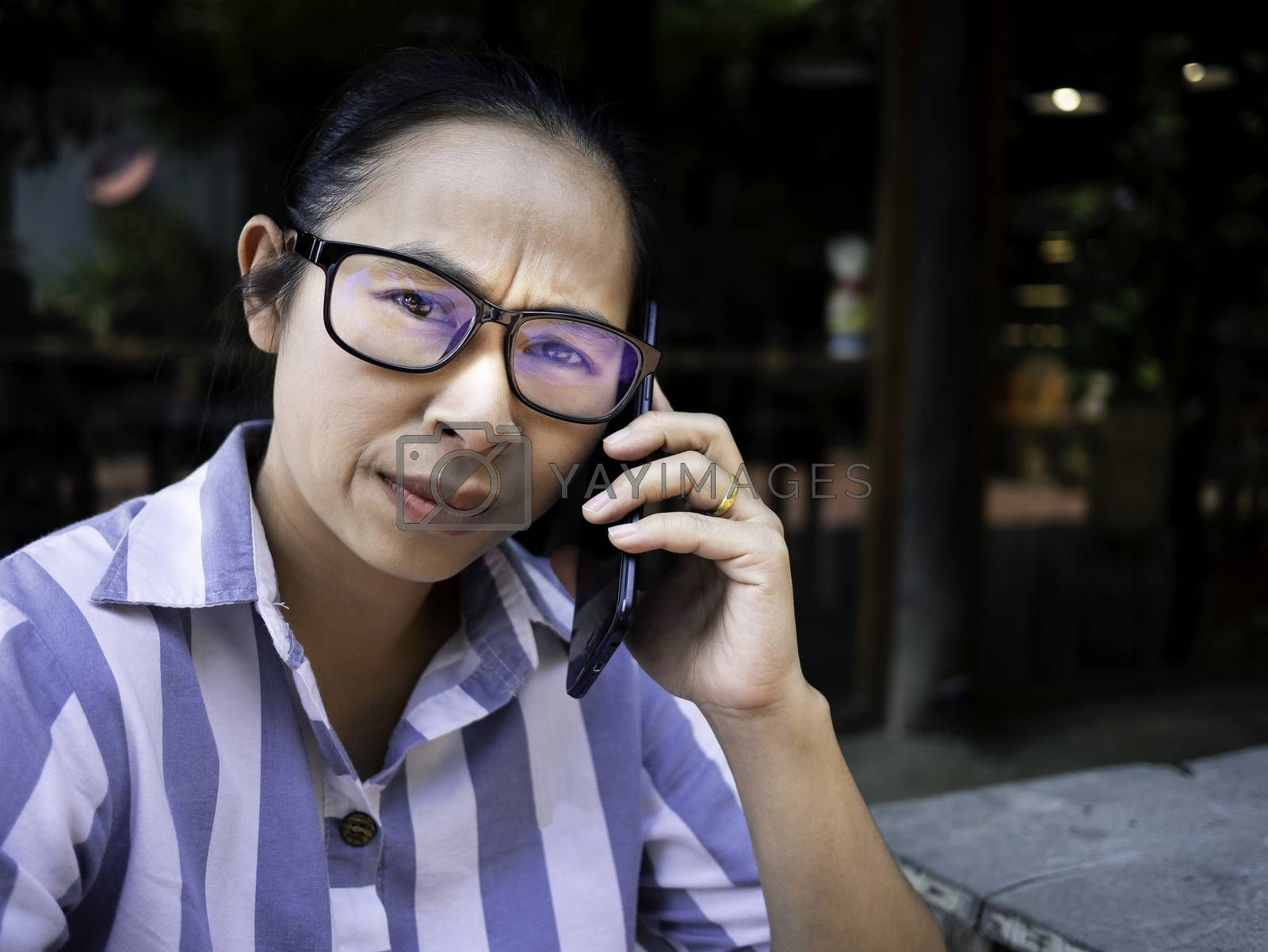 Stressed Asian young woman talking on the phone at coffee cafe. by TEERASAK