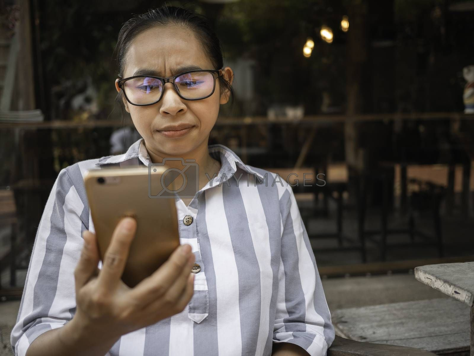 Stressed Asian women sitting on wooden chair with smartphone in coffee cafe. Health and medical concept. by TEERASAK