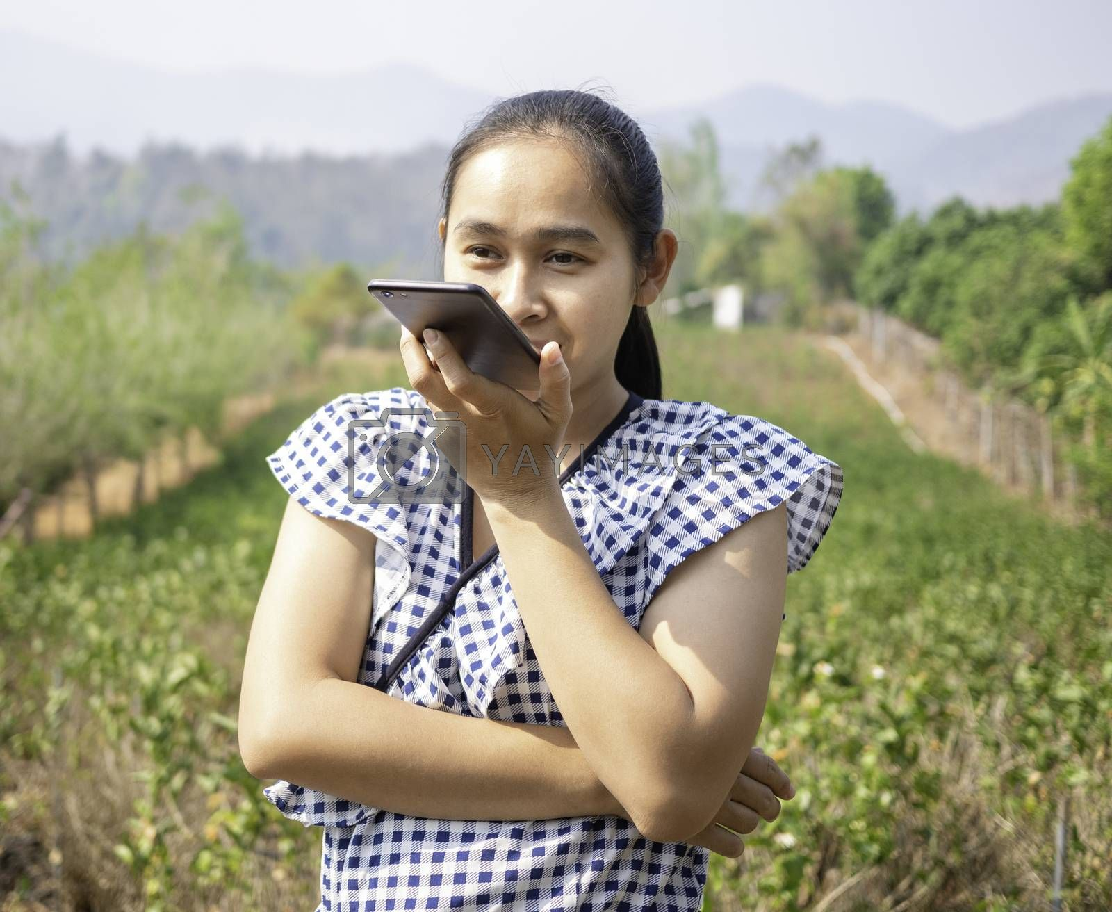 Asian young women talking by speaker phone in the jasmine garden while sunshine to the face. by TEERASAK