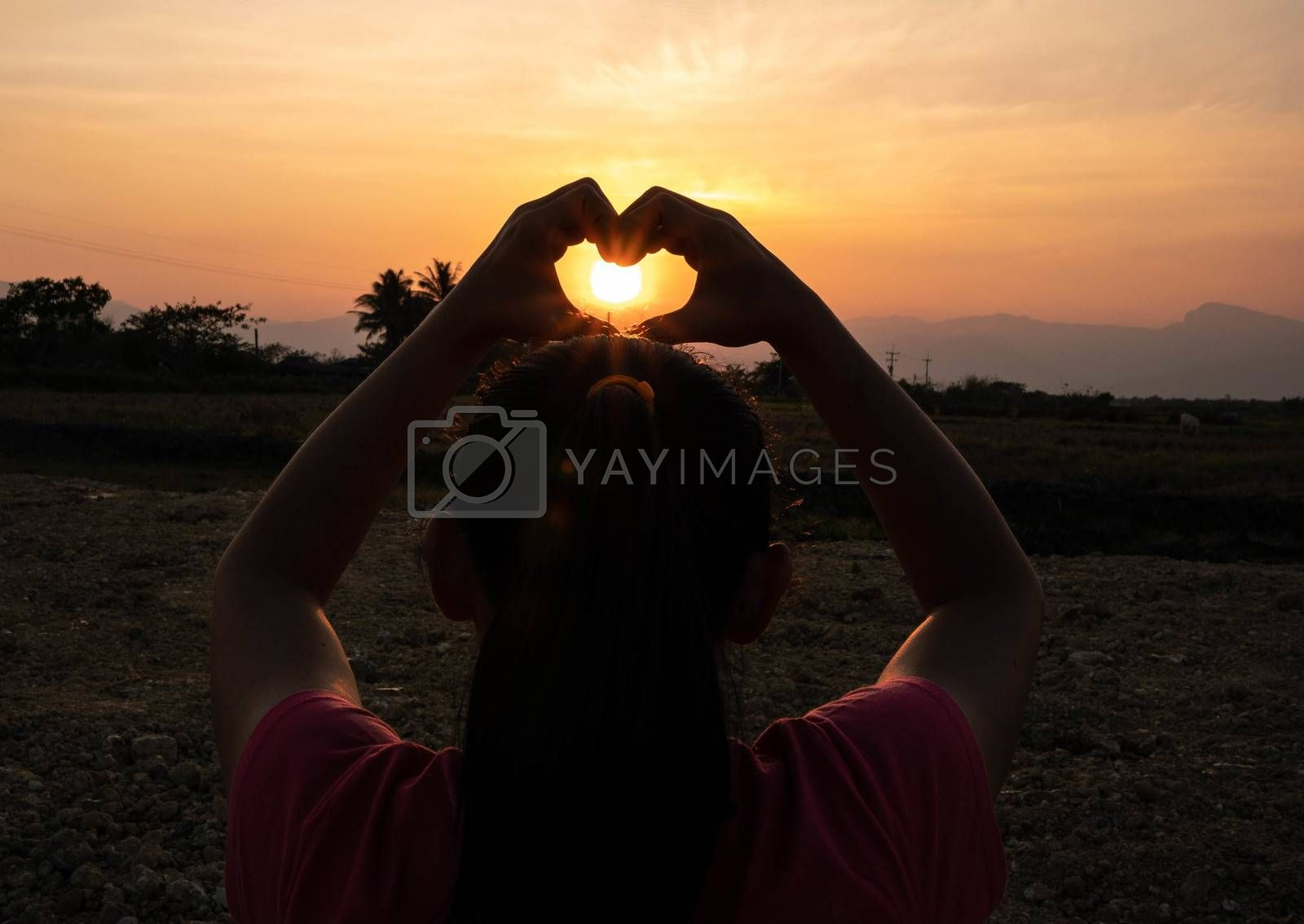 Asian young woman making heart shape by hands on the sunset by the field.
