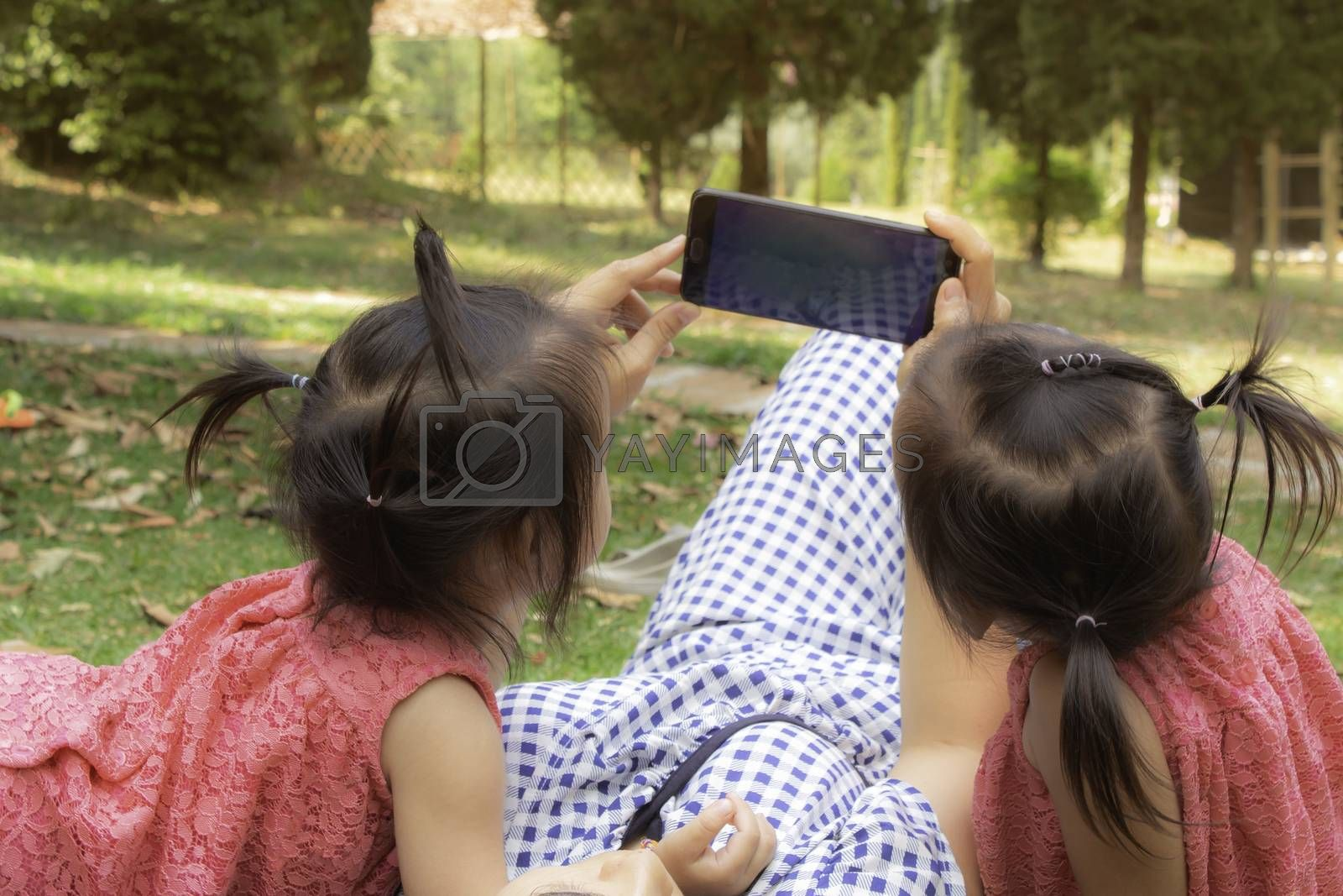 Asian mother and her daughters sitting on the grasses ground in the garden and looking at smartphone happily.