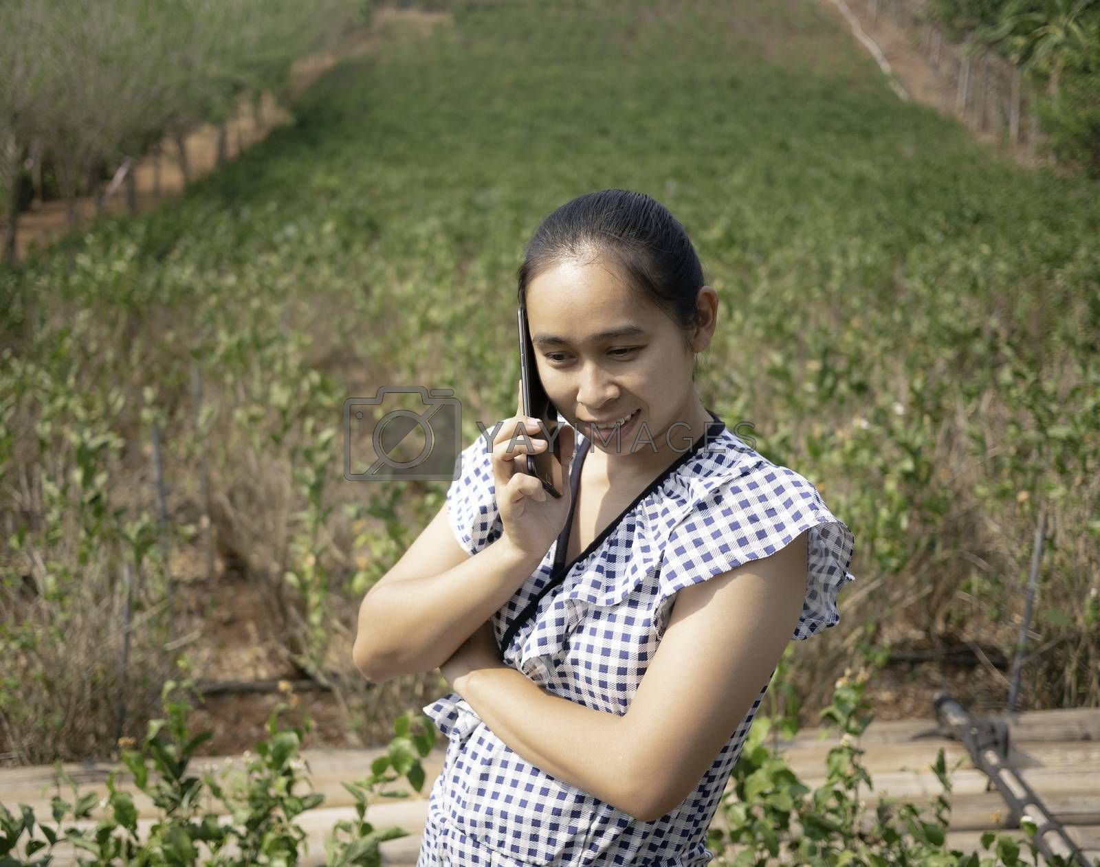 Asian young women talking by phone in the jasmine garden and use hand to protect sun shines  to the face.