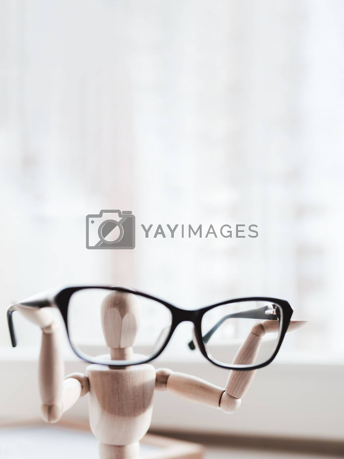 Wooden dummy with eyeglasses in hands. Mannequin presents glasses as a help for comfort life in case of  poor vision. Miniature model of human as concept symbol of ophthalmology.