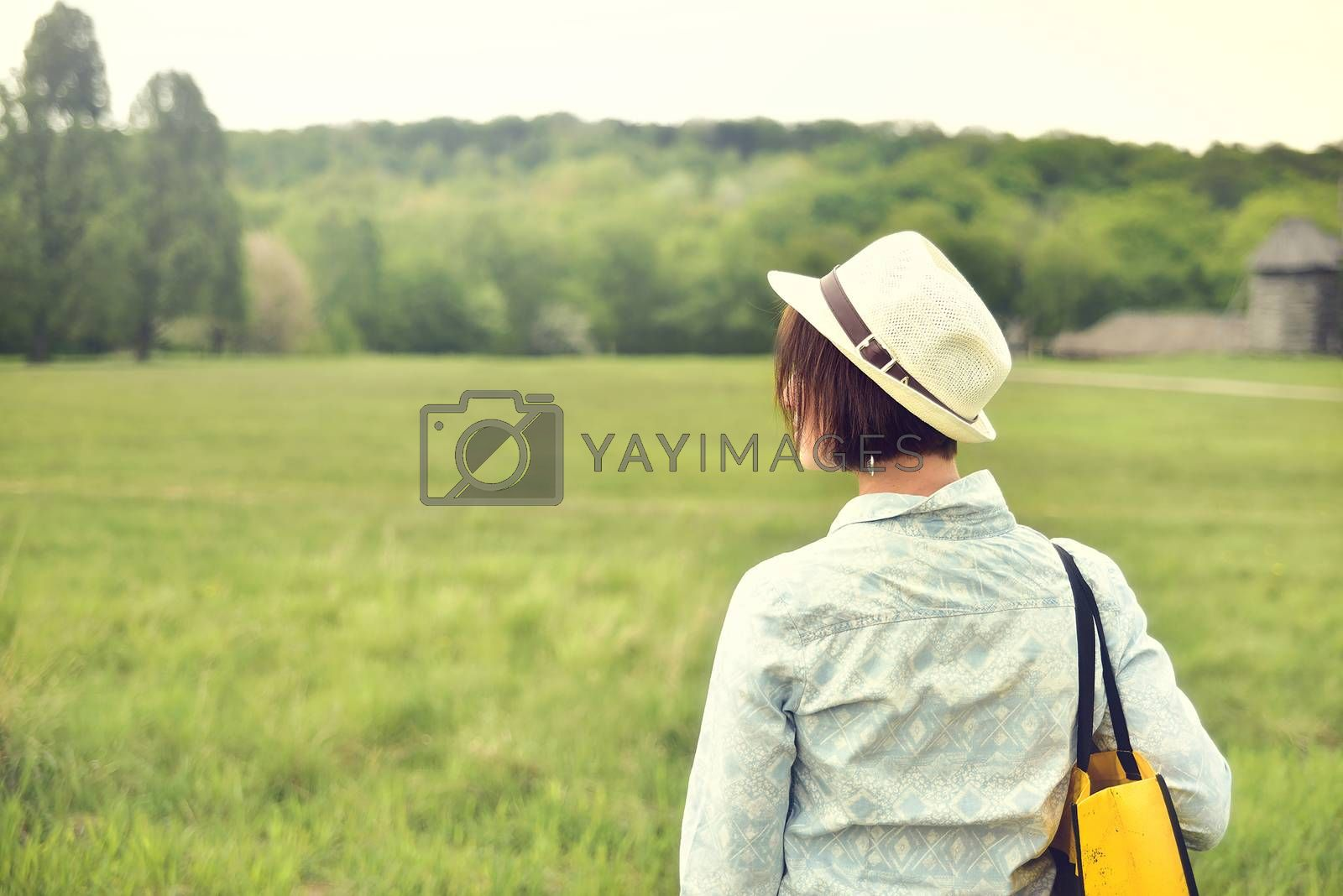 Back view of brunette woman wearing shirt , straw hat and bag walks on the summer field. nature