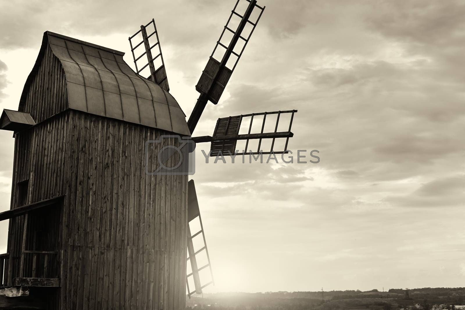 Old windmill standing alone in the field with the blue sky on the background with copyspace. retro filter by Nickstock