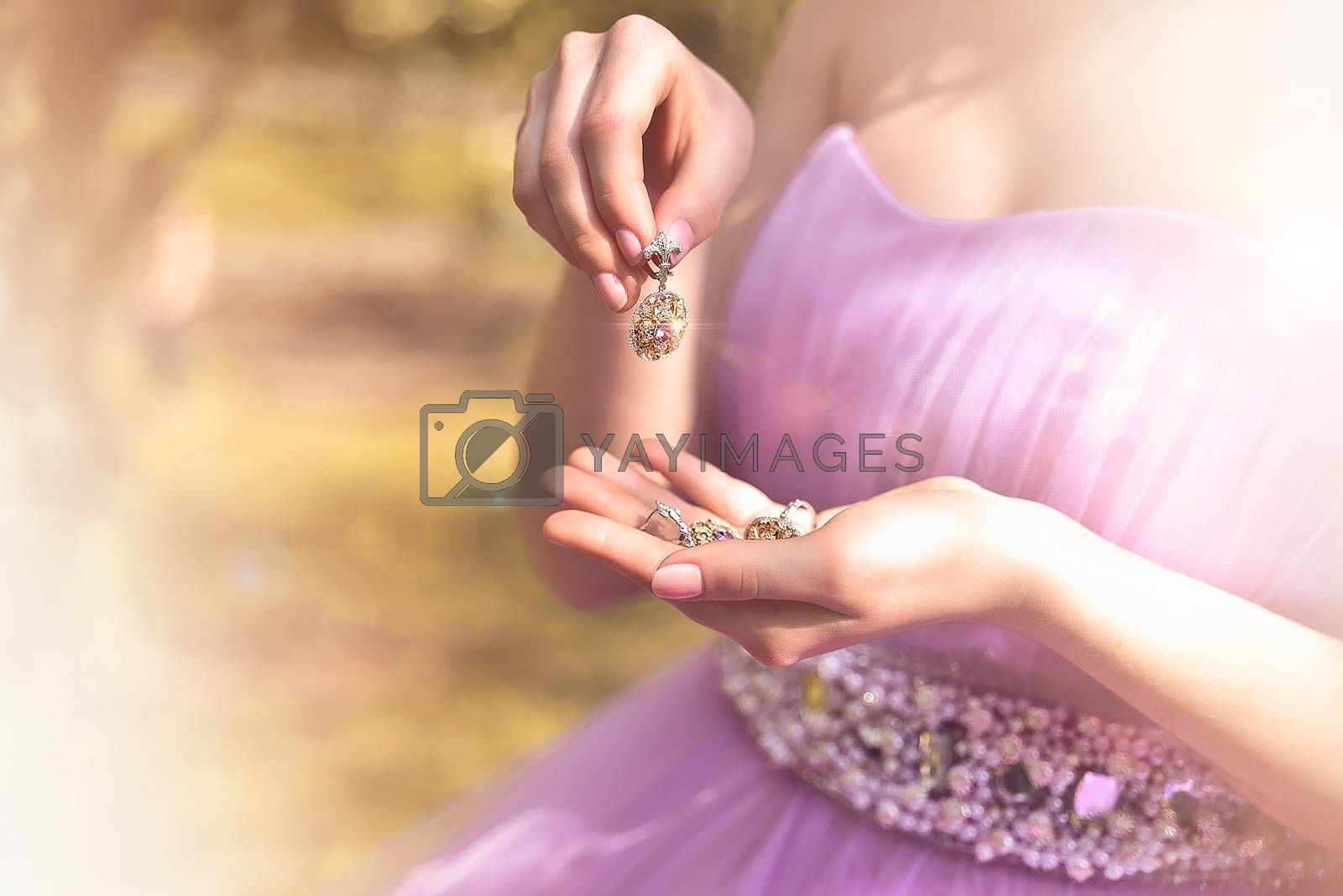Wedding jewels in female hands close-up. vintage dress. nature. fashion. by Nickstock