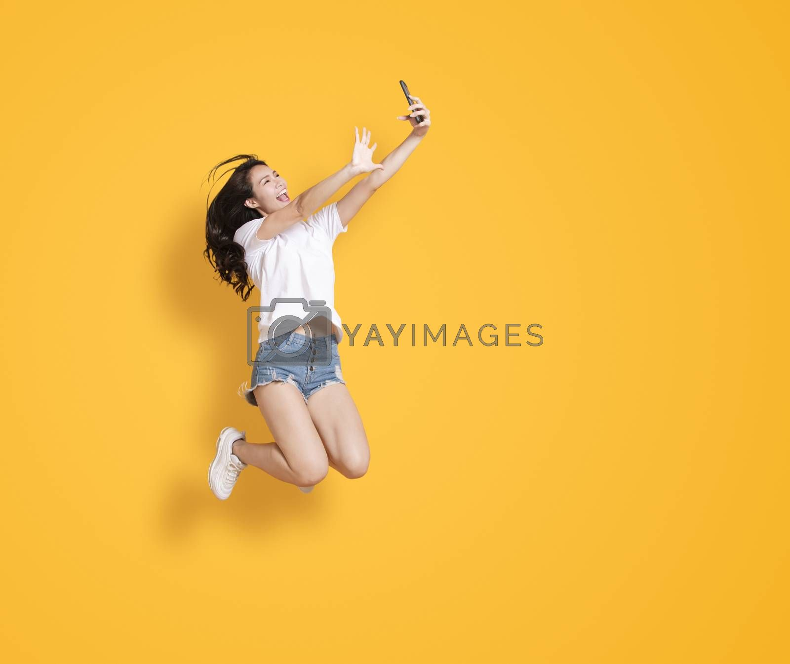 young woman jumping while taking selfie by mobile phone