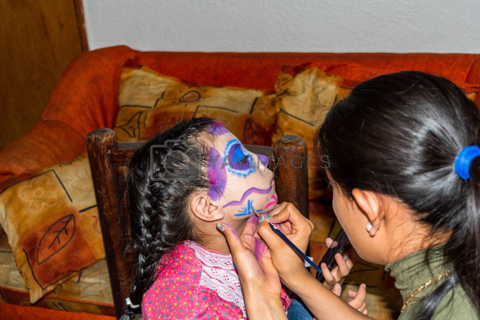 Young woman putting makeup of Catrina in a girl's face by Tonhio
