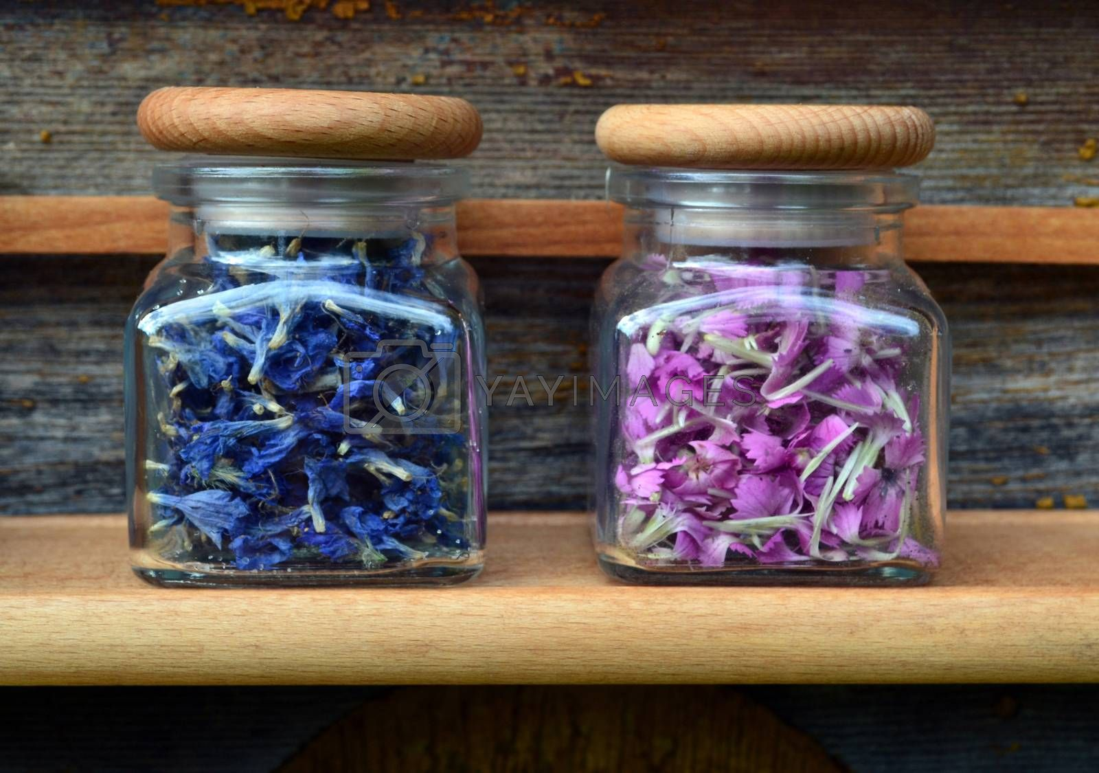 Pink and blue flowers in transparent jars