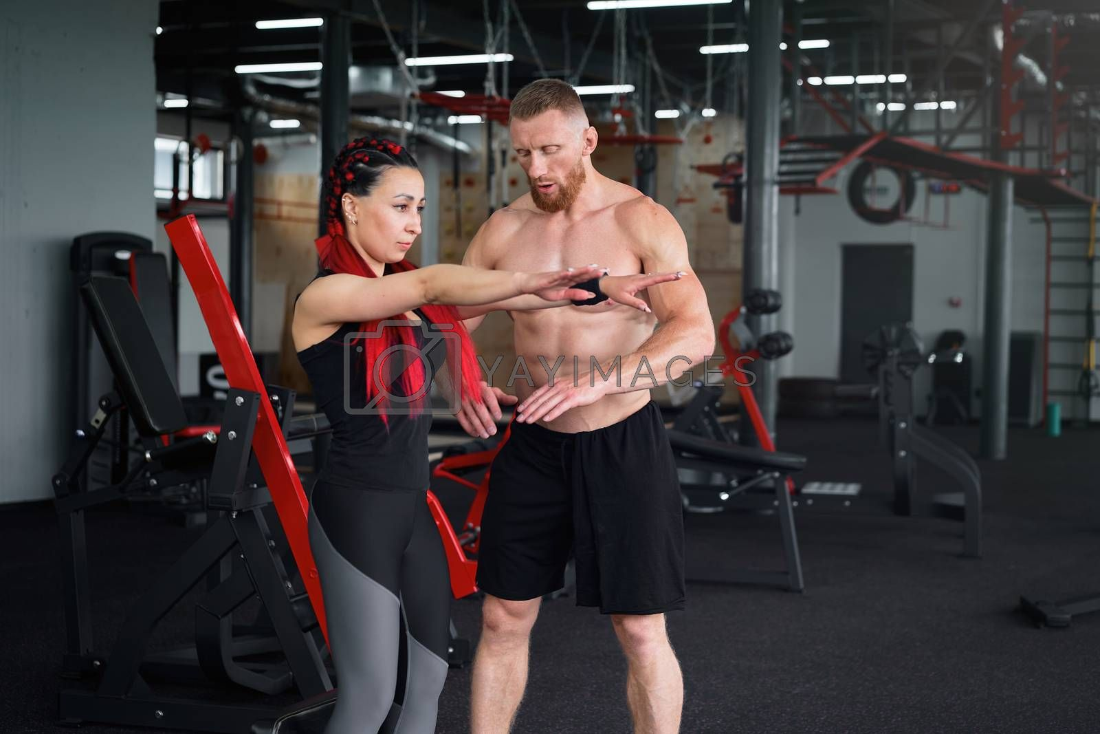 Personal trainer coach instructor athlete sportive man woman gym Boyfriend girlfriend training together Middle adult handsome sportsman people fitness exercising indoors. squats