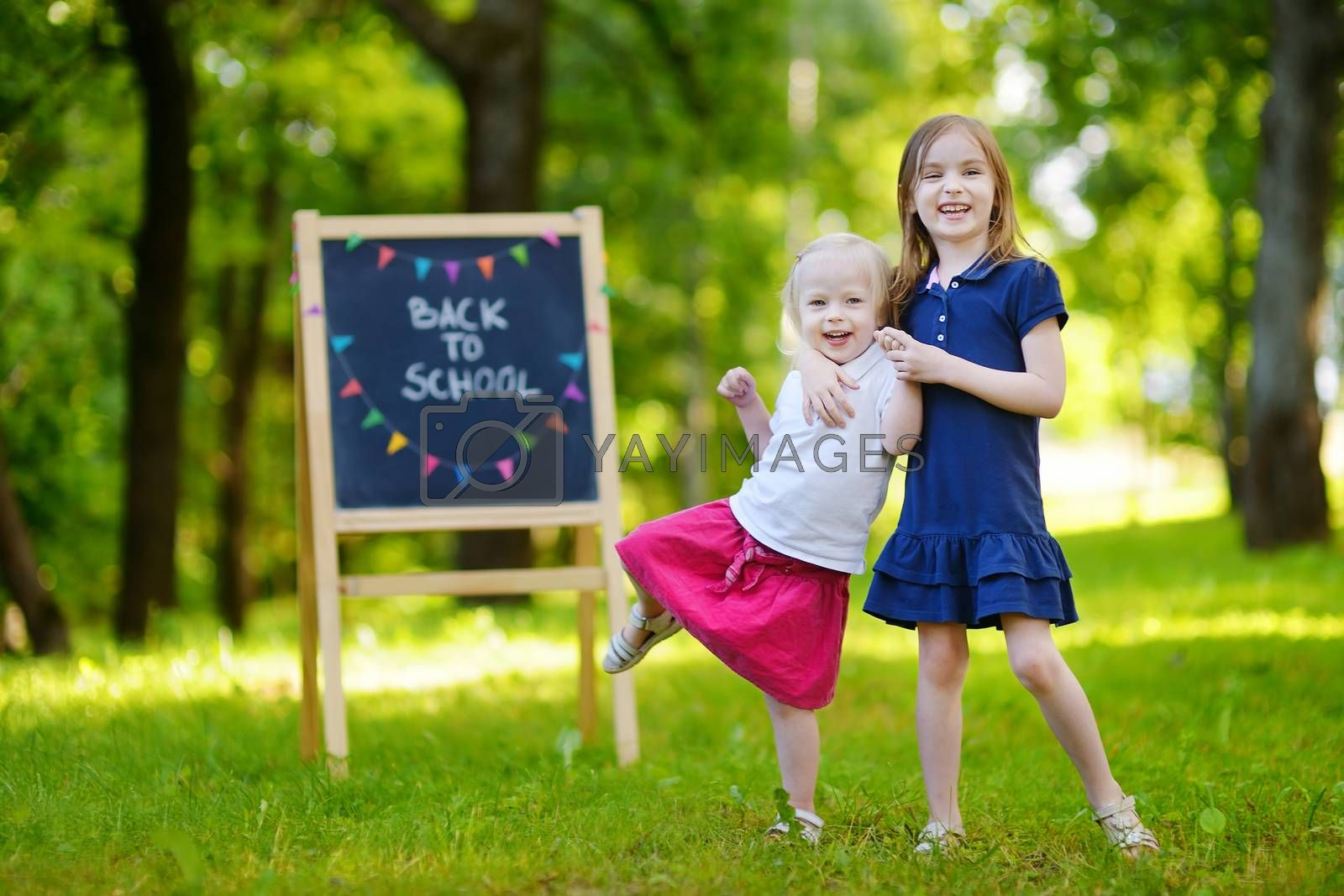 Two adorable little sisters feeling very excited about going back to school