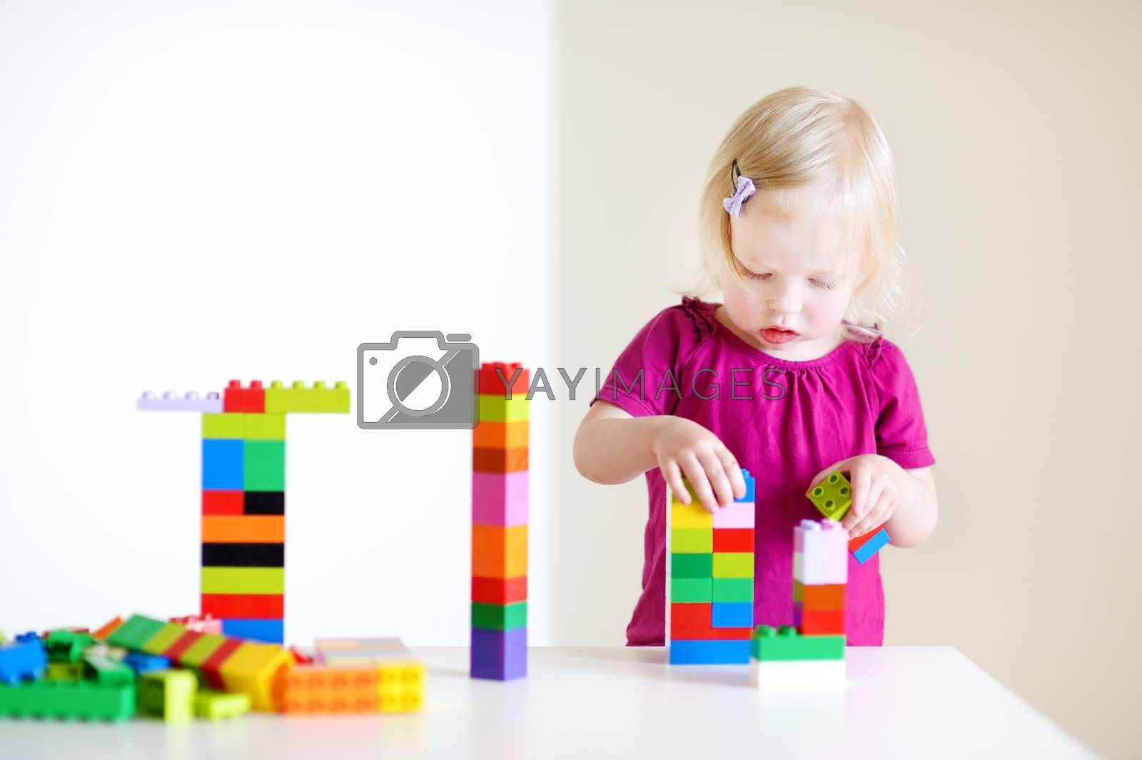 Cute little toddler girl playing with colorful plastic blocks at home