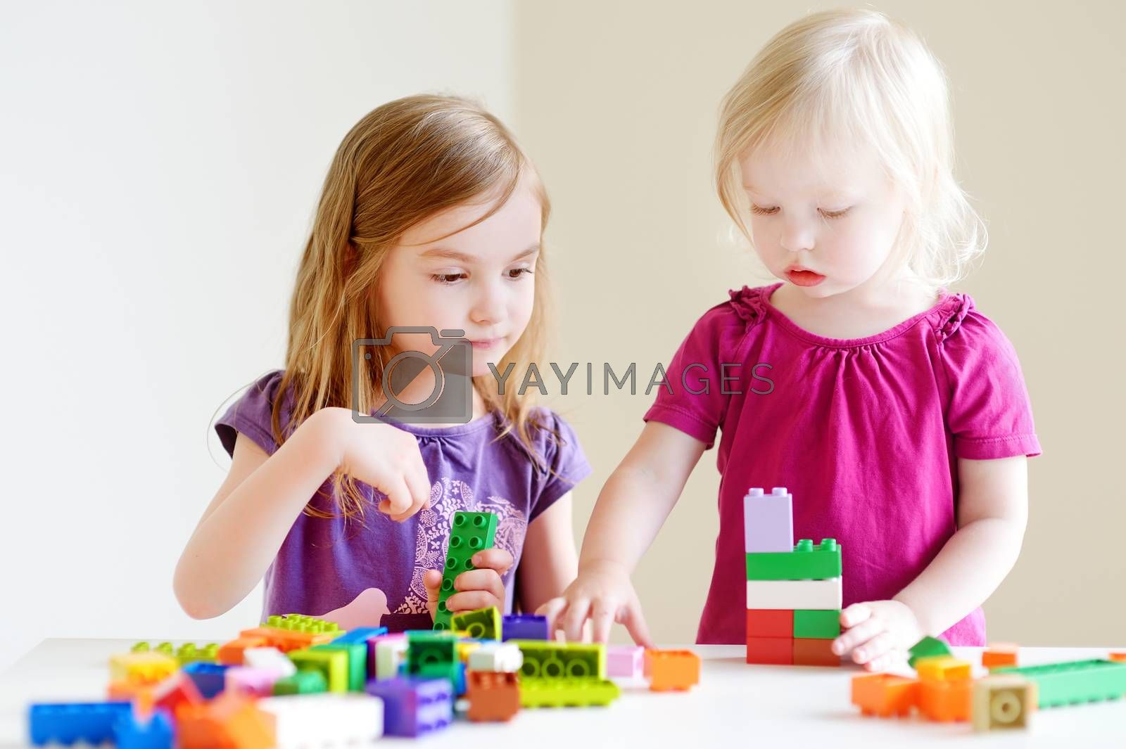 Two cute little sisters playing with colorful plastic blocks at home