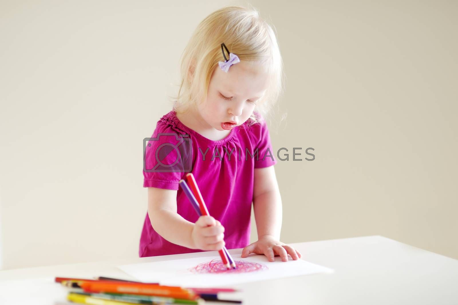 Cute little toddler girl trying to draw a picture with several pencils at once
