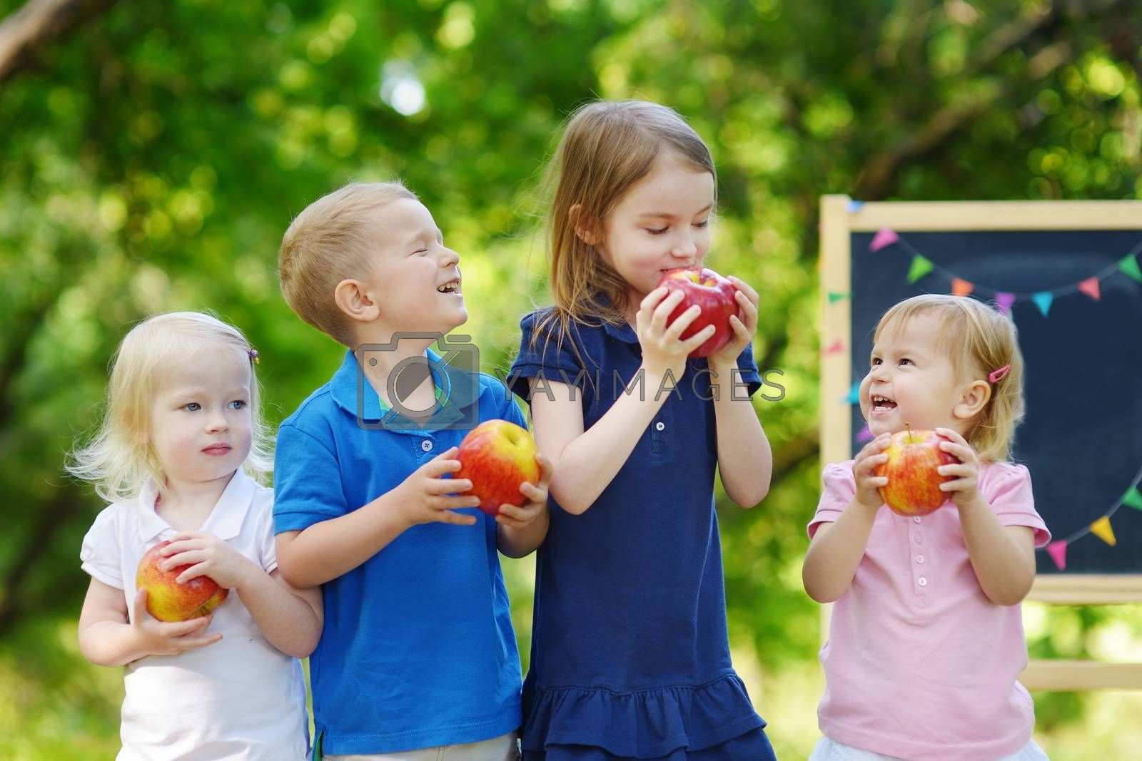 Four adorable little kids holding healthy organic apples in summer park on beautiful sunny day