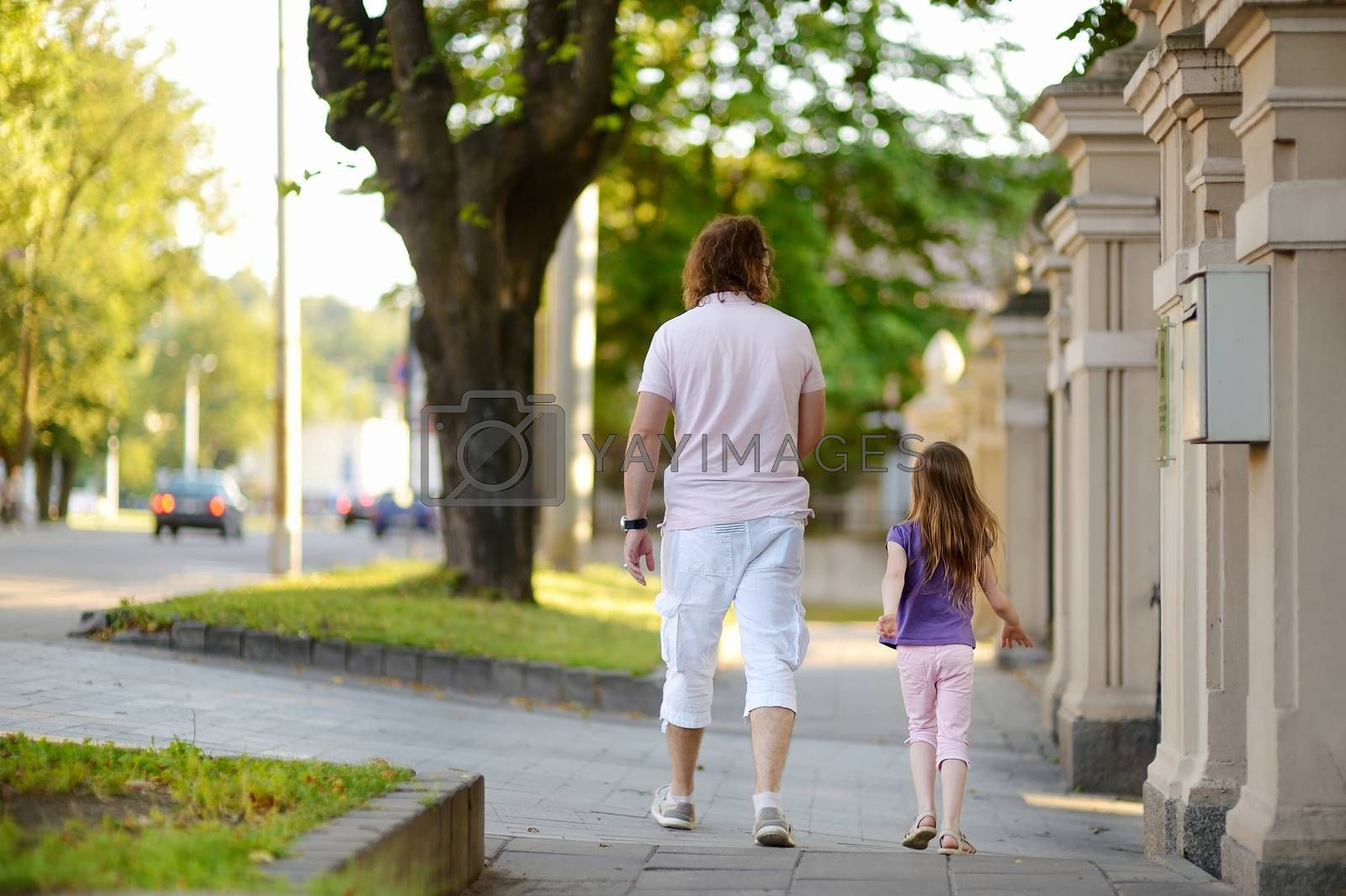 Father and daughter having a walk in a city