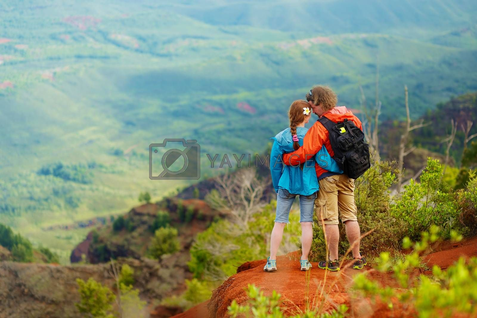 Two hikers relaxing enjoying the amazing view from the mountain top