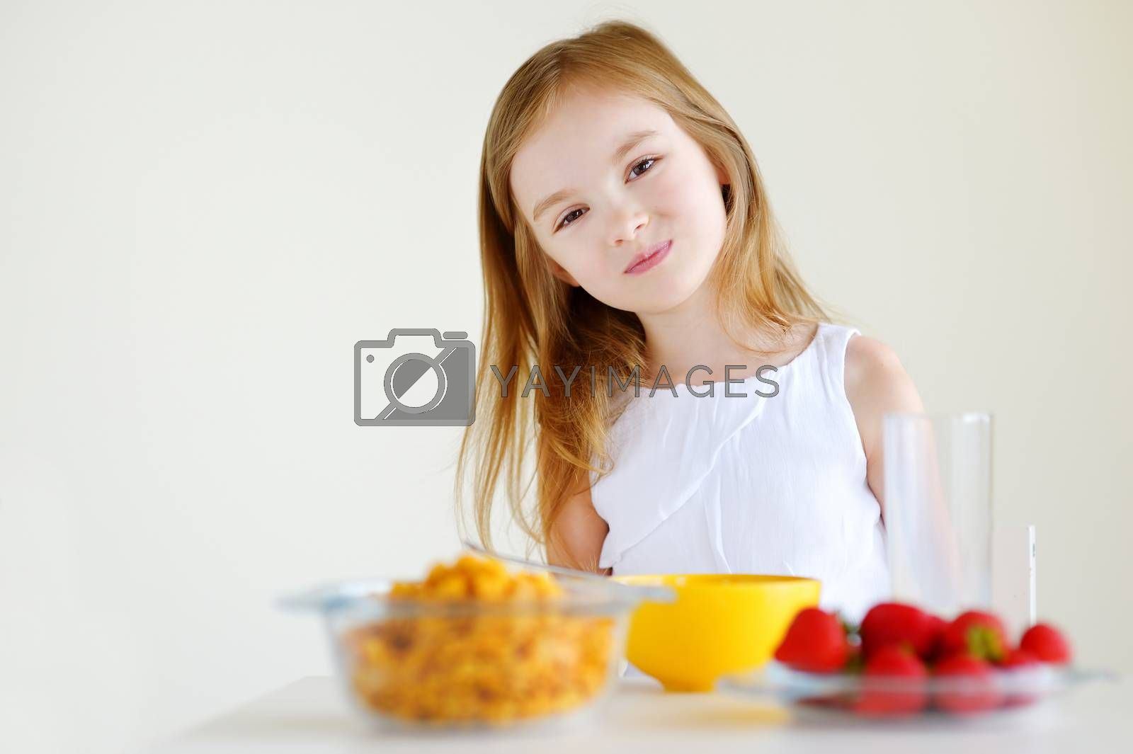 Adorable little girl eating cereal with strawberries and drinking milk in white kitchen