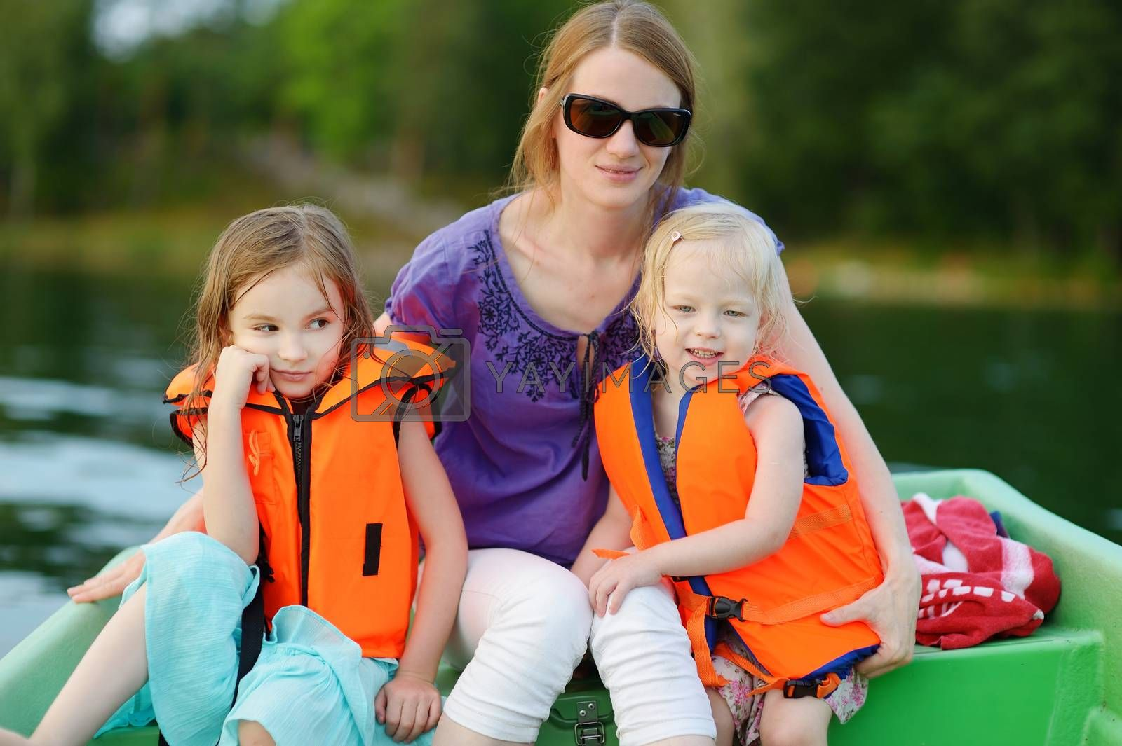 Young mother and her two little daugthers on a boat on warm and beautiful summer day