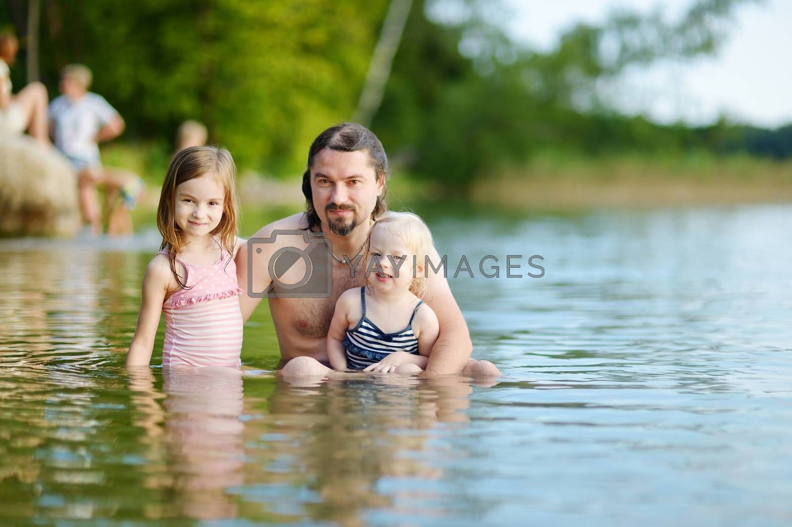 Two little sisters and their father having fun in a river at summer