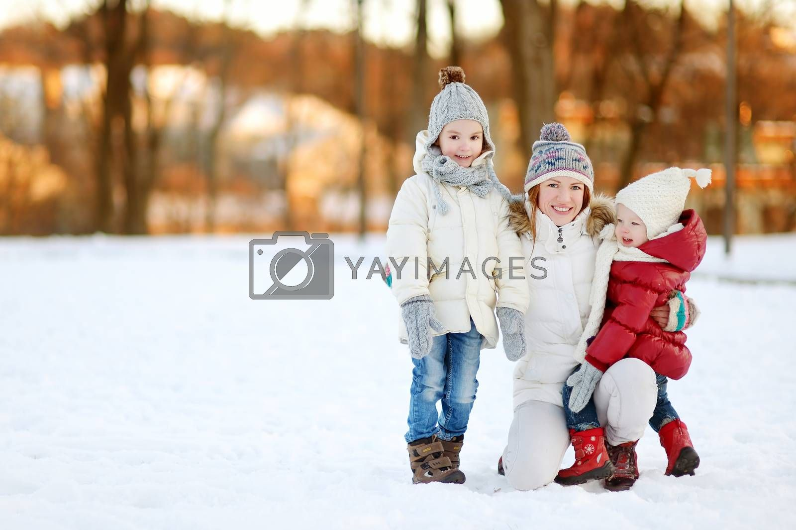 Young mother and her two daughters having fun on winter day