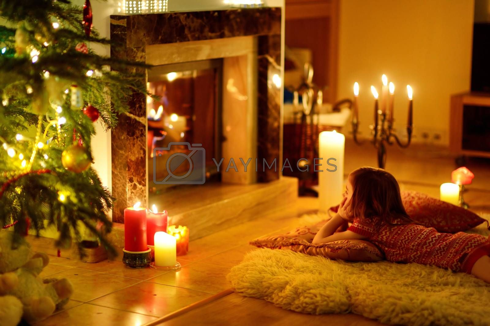 Happy little girl sitting by a fireplace in a cozy dark living room on Christmas eve