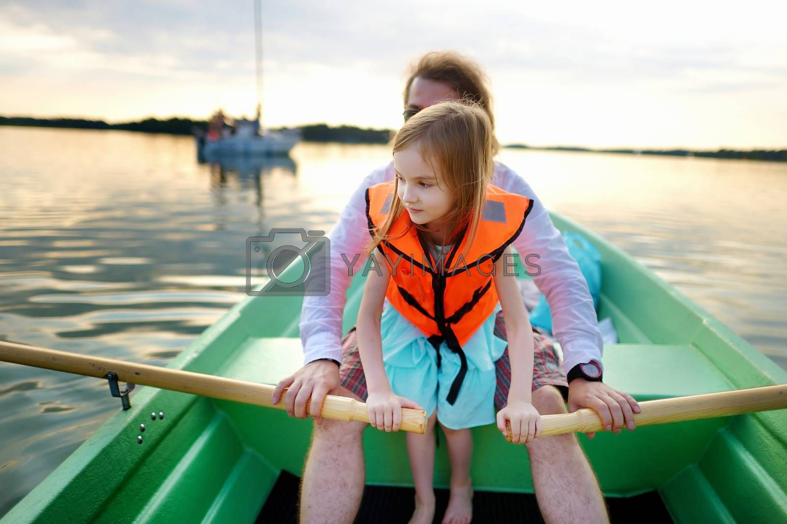 Little girl with her father on a boat on warm and beautiful summer day
