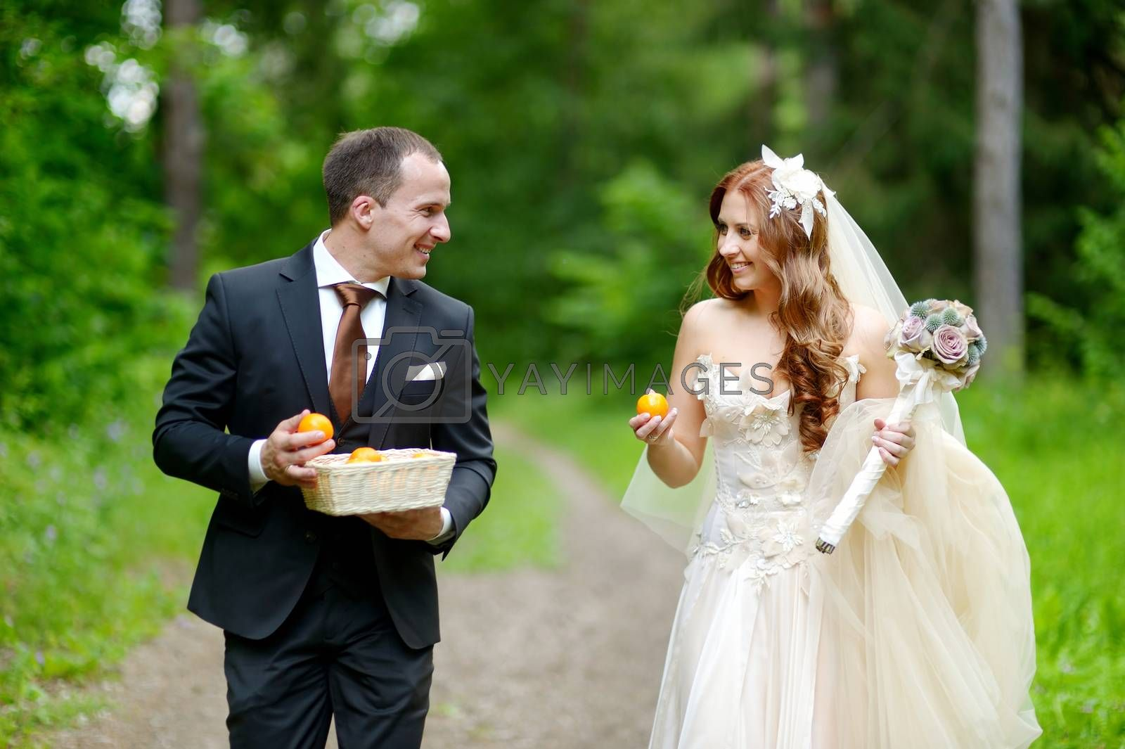 Young bride and groom taking a walk in beautiful summer park