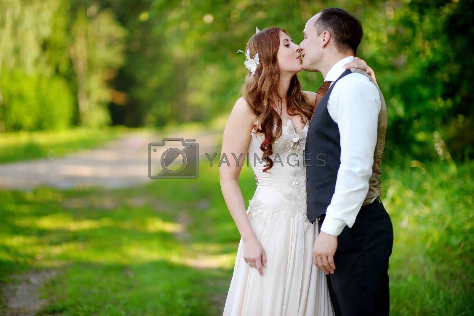 Young bride and groom hugging and kissing in beautiful summer park