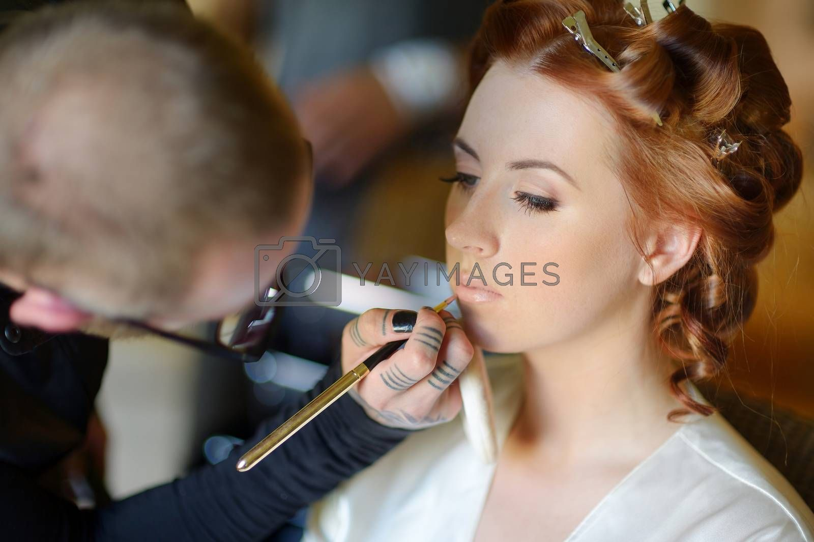 Young beautiful bride applying wedding make-up by professional make-up artist