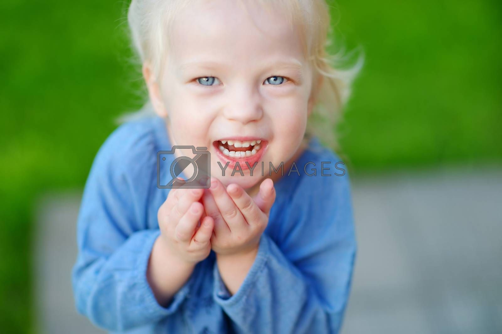 Cute little girl having fun running and laughing on a sunny summer day