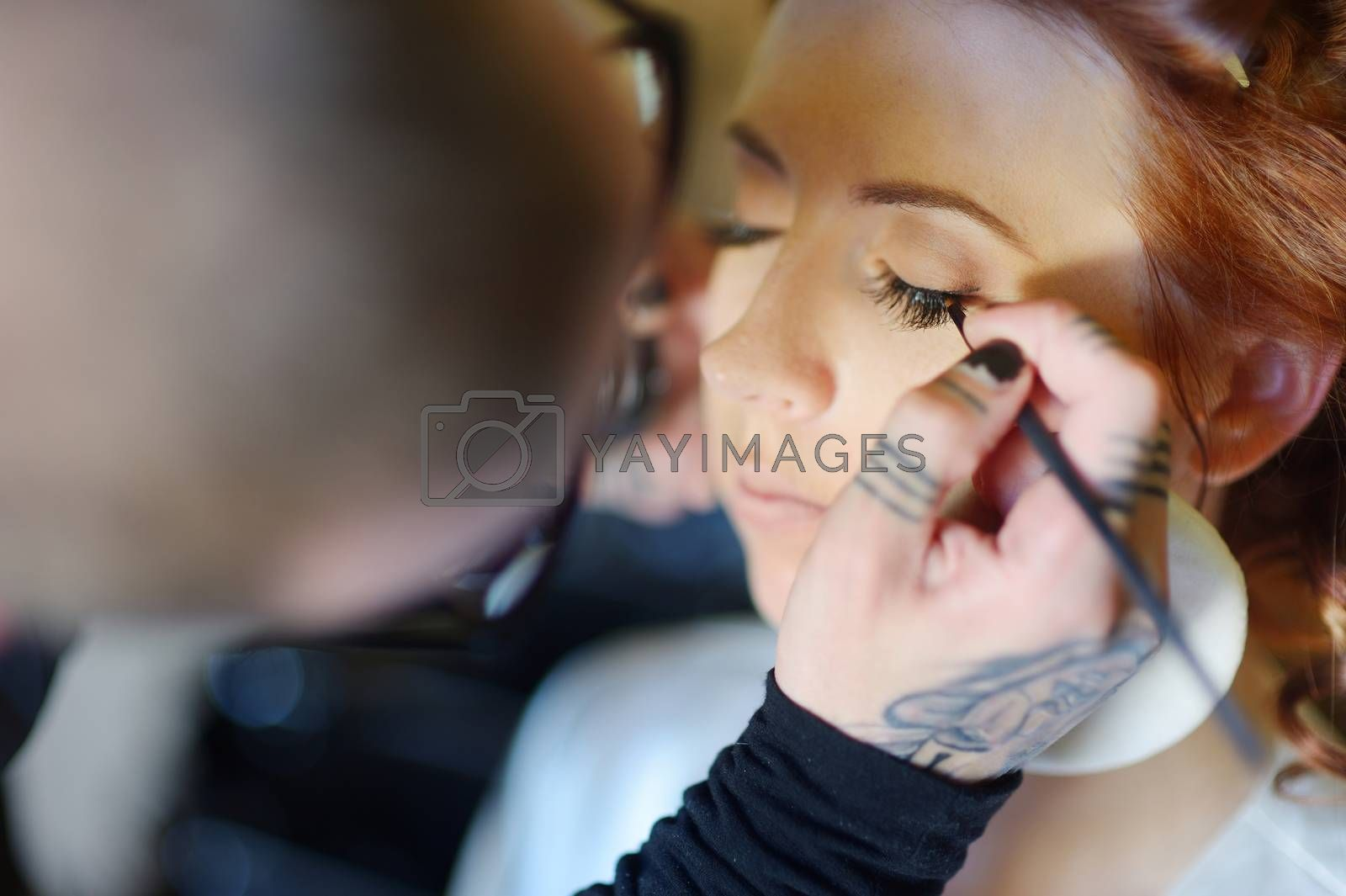 Royalty free image of Young beautiful bride applying wedding make-up by maximkabb