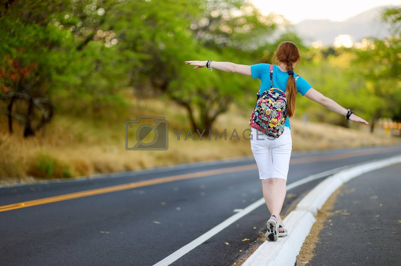 Young tourist with a backpack hitchhiking along a road