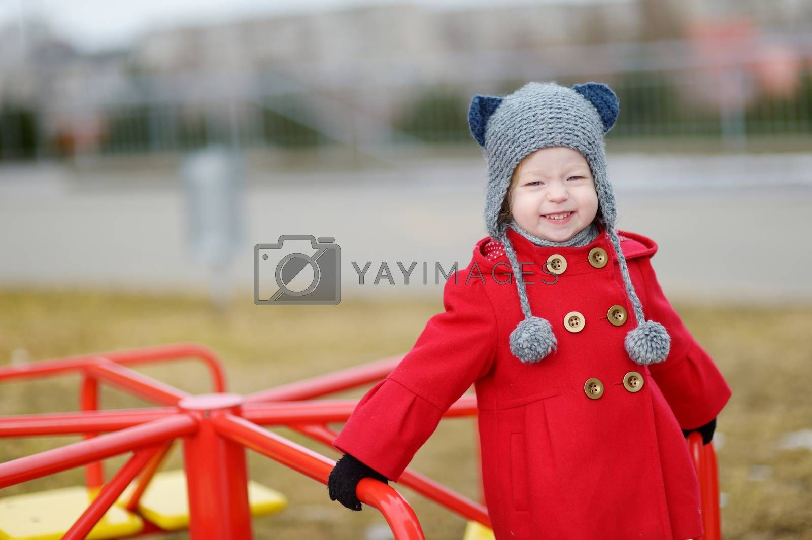 Adorable girl having fun on a playgroud on beautiful spring day