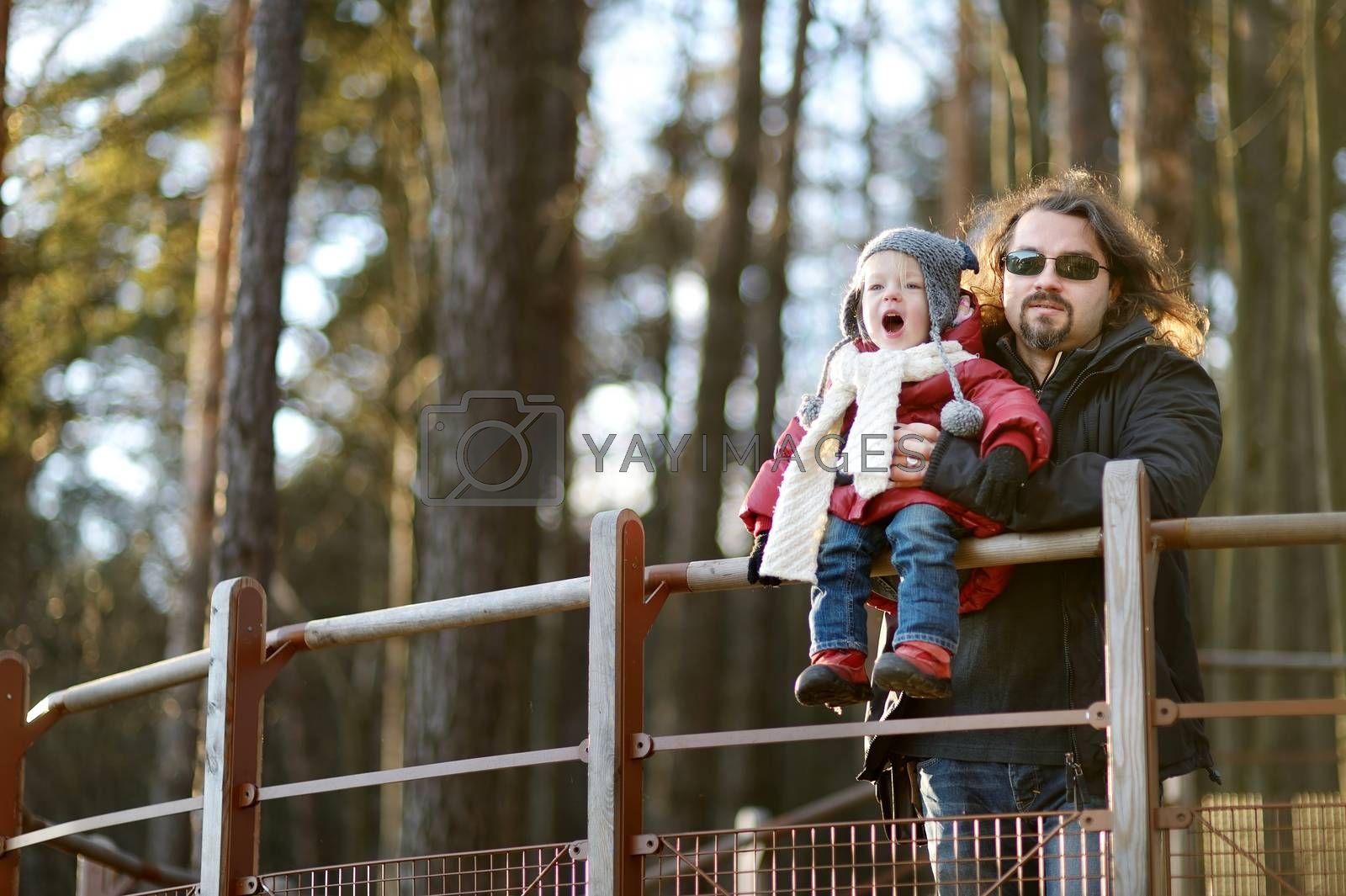 Young father and his little daughter enjoying a view on beautiful winter day