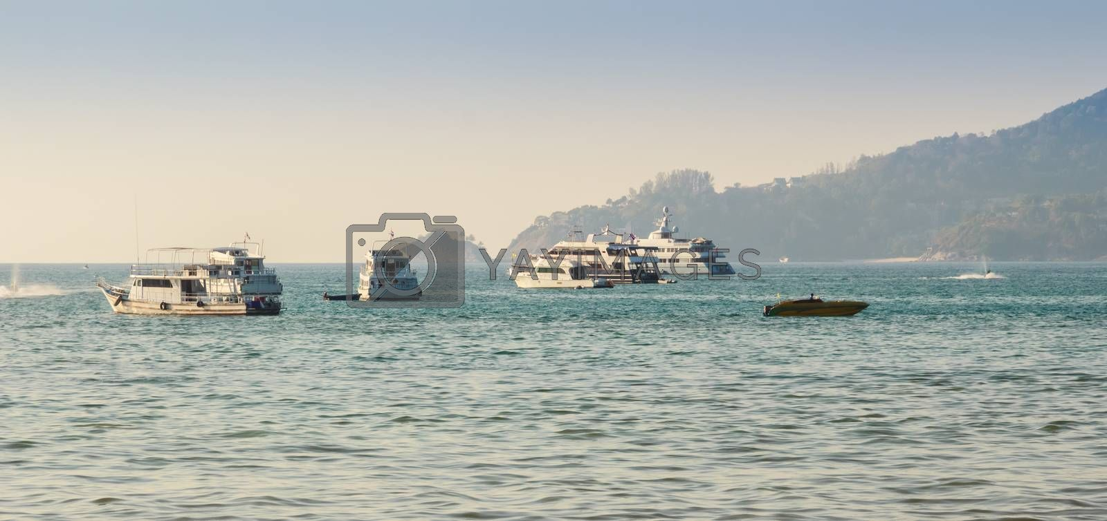 Beautiful scenery view of Patong beach in blue sky daylight and mountain background with local fisherman long tail boats and tourist luxury cruises. Patong is the popular beach in Phuket, Thailand.