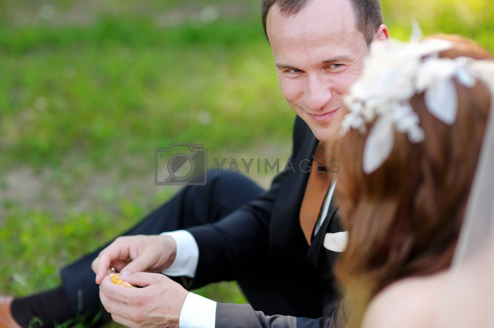 Young bride and groom sitting on a grass in beautiful summer park