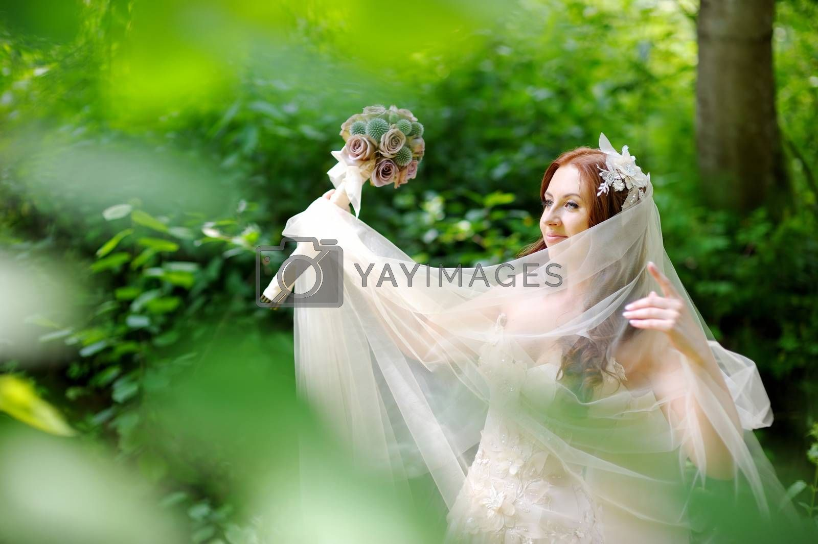 Young beautiful bride posing in beautiful summer park