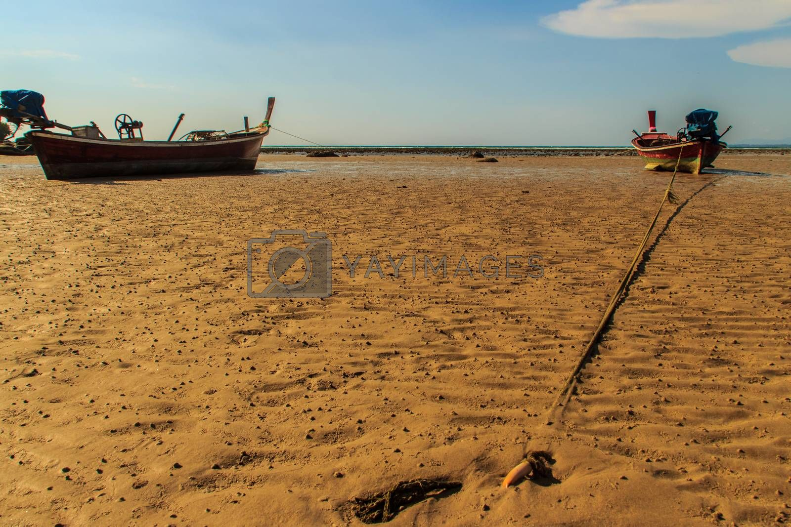 Traditional Thai wooden longtail boats (Rua Hang Yao) moored on the sand at small pier with blue sky and small island background in Phuket, Thailand