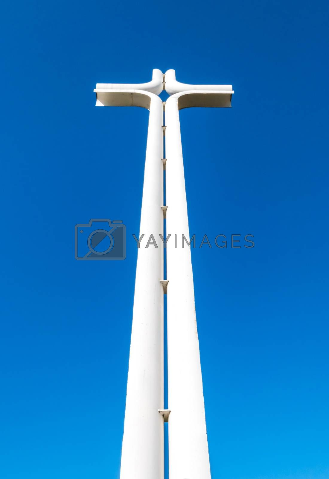 Modern iron cross of white color, isolated on a blue sky background.