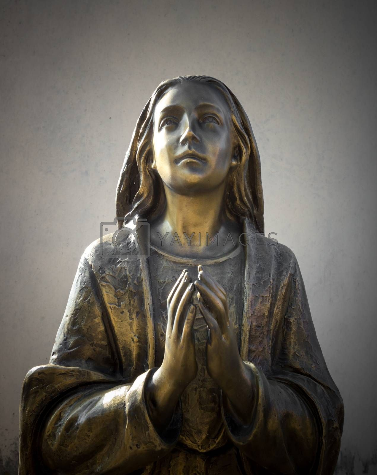Holy Mary statue bronze that prays with folded hands, in the background a gray wall. It can be used for events, concepts and backgrounds.