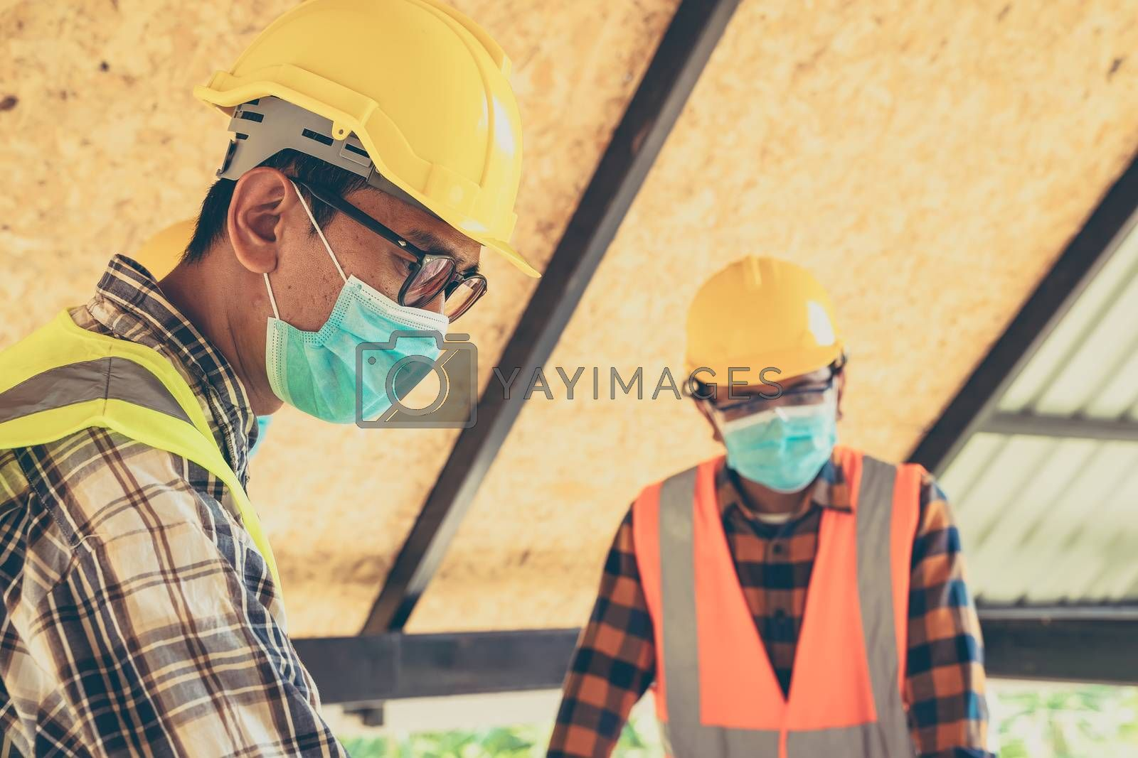 Engineer wearing protective mask working and meeting at construction site.