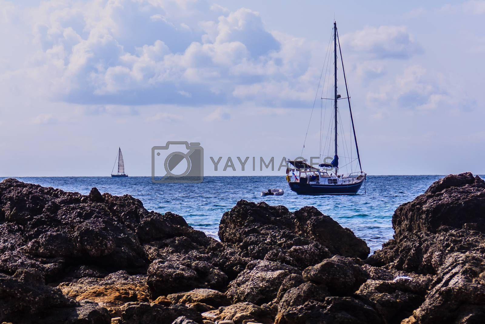 Colorful marine landscape with sail boat against deep blue sea under blue sky in the ocean on the cloudy day.