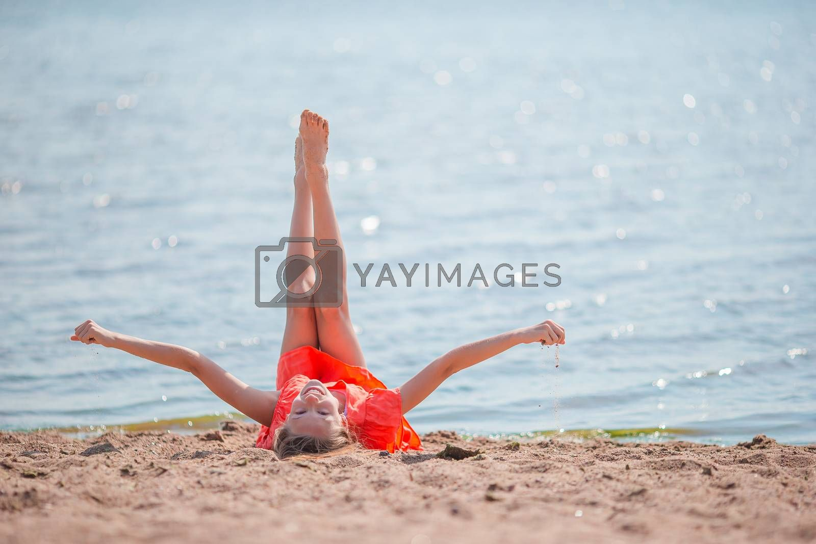 Adorable little girl have fun on the beach. Young beautiful kid on the Gulf of Finland in the St. Petersburg area in Russia