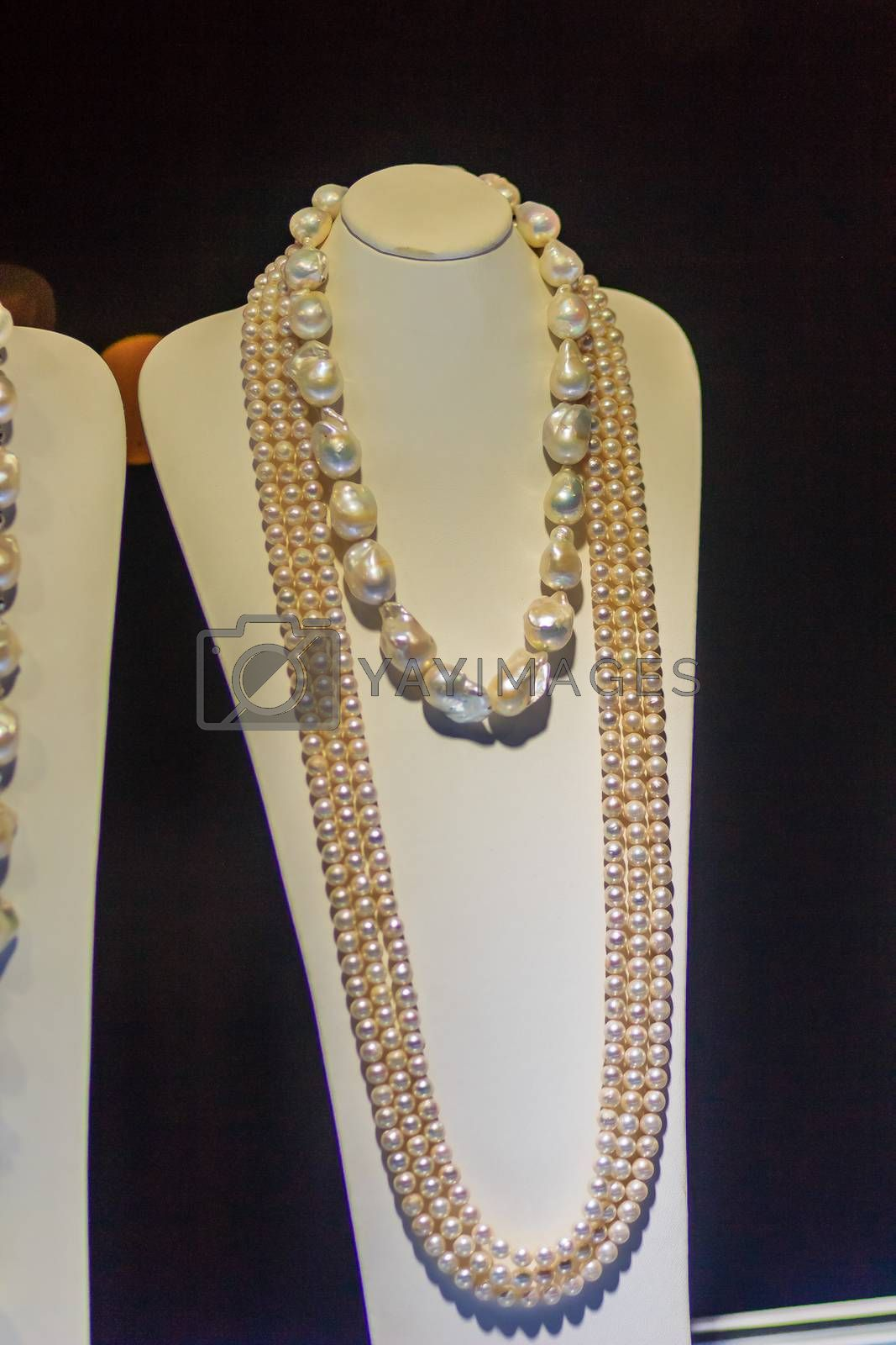 Beautiful long pearl necklaces are displayed at a jewelry shop. Poor light with noise grain shot