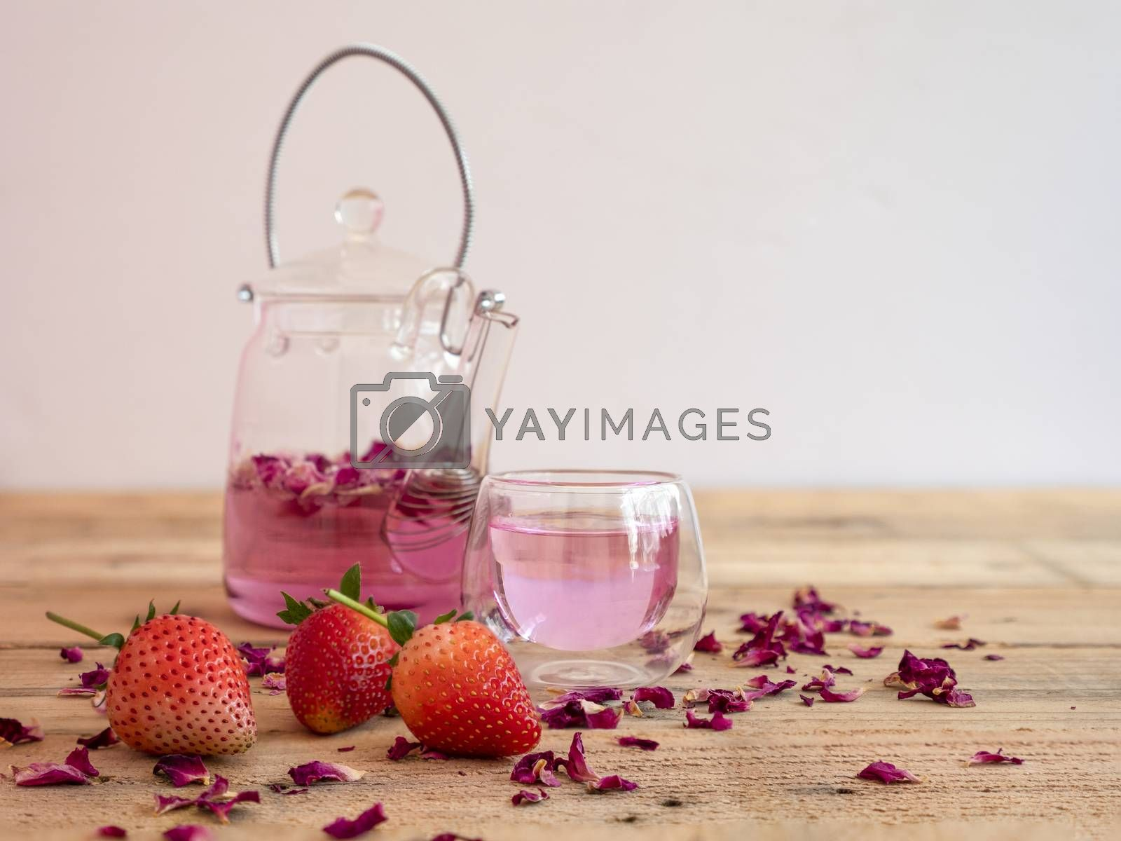 Pink rose petals infusion tea in a small clear drinking glass with glass kettle. Wooden rustic background.
