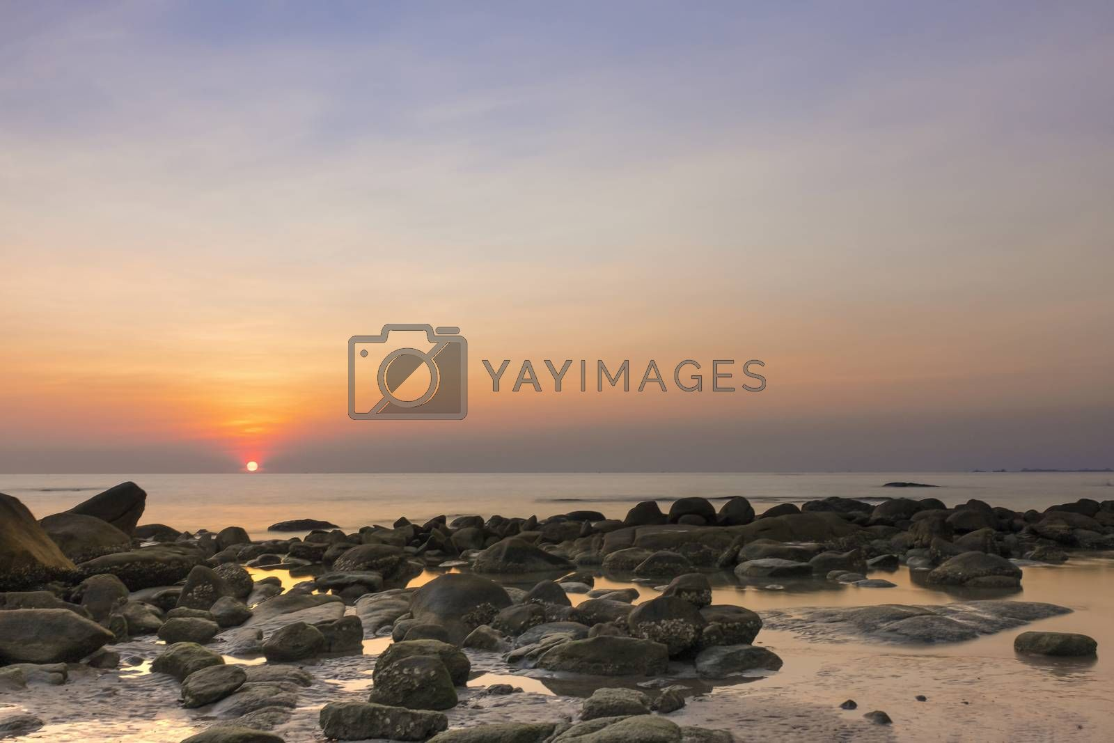 Moment of sunsetting with gloden sphere of light just touching the sea level in the horizon.
